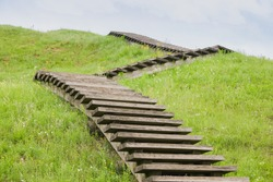 A green Zig Zag stairs uphill. Concept growth on grass