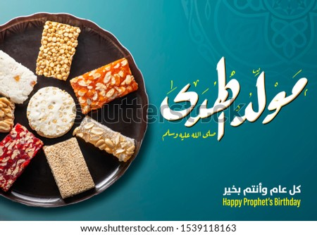 """A Greeting Card of Traditional Sweets, Arabic Text Saying """"Bith of The Guider Peace Be Upom Him, Happy Prophet Muhammad's Birthday"""""""