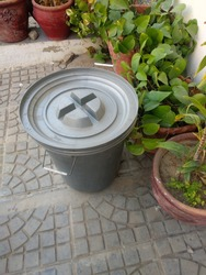 A grey colored plastic bin for garbage near planting pots
