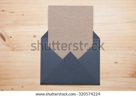 A grey envelope on the wood desk, top view at the studio.