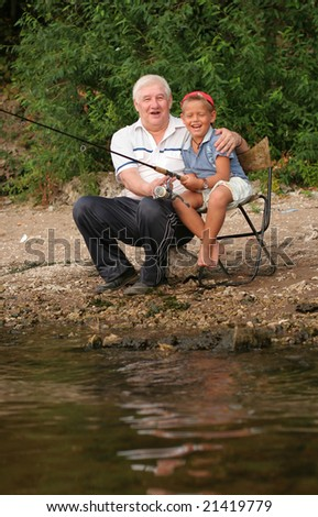 A grey-headed grandfather with a grandson on fishing
