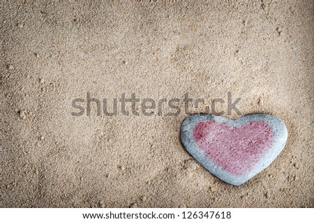 A grey heart shaped stone on grainy sand, tinted with a pinkish red heart.  This version is vignetted and edited to give a retro or lo-fi appearance.