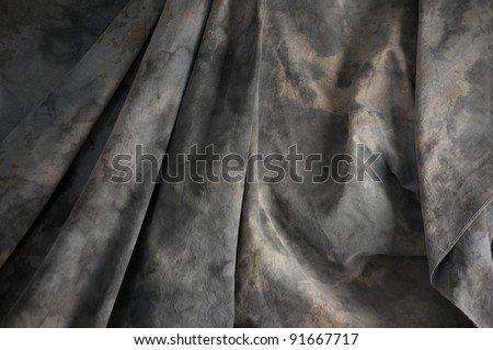 A grey mottled photographer's background cloth fills the image with draped folds.