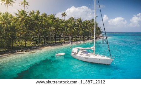 A grey-white sailing yacht anchoring in crystal clear turquoise water in front of the paradisiacal San Blas Islands in Panama with green palm trees in the background. #1138712012
