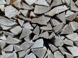 A greyscale closeup shot of firewoods stacked on each other