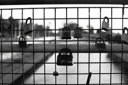 A greyscale closeup shot of many locks on a grid fence