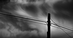 A greyscale low angle view of the electric wires on the metal poles outside on a gloomy day