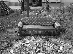 A greyscale shot of a comfortable sofa in the backyard of a house