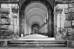 A greyscale shot of a concrete ancient building with a long hallway