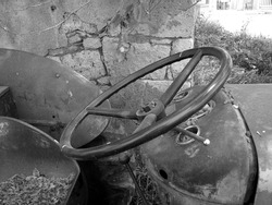 A greyscale shot of a steering wheel of an old tractor