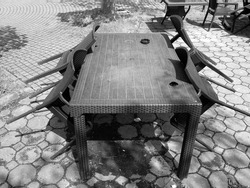 A greyscale shot of a table with chairs laying on it in a garden