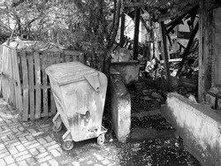 A greyscale shot of a trash can in front of the ruins of old buildings in Sakarya, Turkey