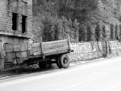 A greyscale shot of a wooden truck trailer on the street