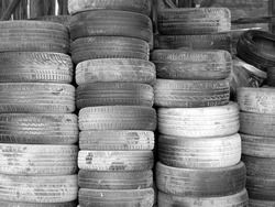 A greyscale shot of car tire piles