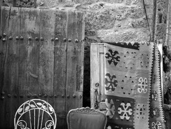 A greyscale shot of the antiques by the wall in a street in Alacati, Izmir, Turkey