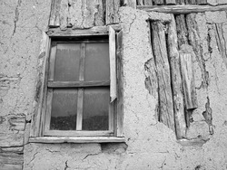A greyscale shot of the window of an old abandoned wooden hut