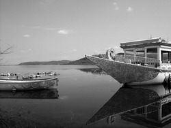 A greyscale shot of two boats in the sea captured during the daytime