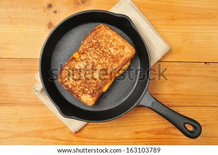 A grilled cheese sandwich in a cast iron skillet photographed from above
