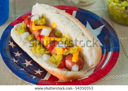 A grilled hot dog on a flag plate with mustard, ketchup, relish, and onions