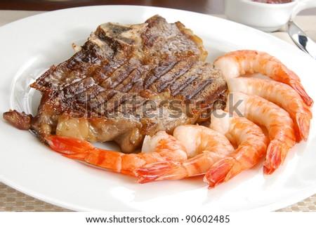 A grilled rib steak and tiger shrimp prawns