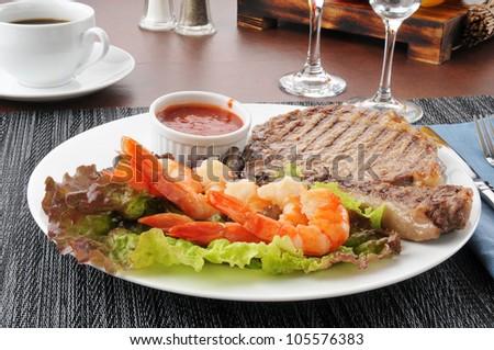 A grilled rib steak with tiger shrimp prawns