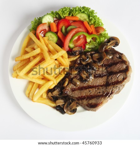 A grilled ribeye steak served with mushrooms,  chips (french fries) and a garden salad of lettuce, cucumber, baby carrot and capsicum, viewed from above