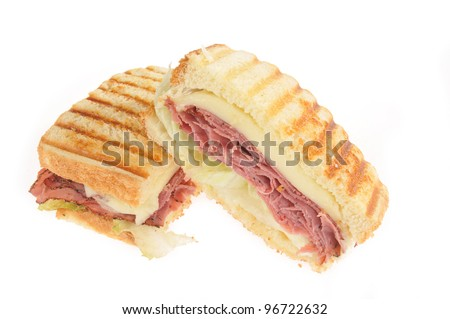 A grilled roast beef panini with swiss cheese on a white background
