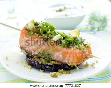 A grilled salmon fillet with grilled eggplant and wine. Shallow depth, selective focus - stock photo