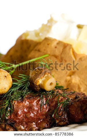 A grilled steak topped with fresh mushrooms and dill for dinner.