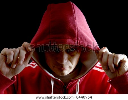 A grim looking Hoodlum lifting his hood with his right arm