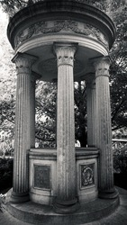 a grimey shot of a columned edifice that was made to celebrate the lives of those who shed their mortal coil.