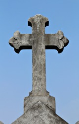 A gritty, grey stone cross in a graveyard. The cross is plain with no marking and there is a small amount of moss on it. The crucifix is shot against a blue sky background.