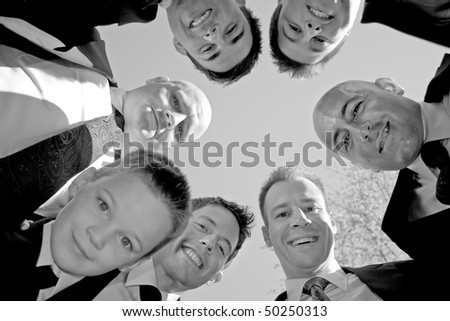 A groom and his groomsmen posing together in a huddle formation.  Shallow depth of field with focus on the men.
