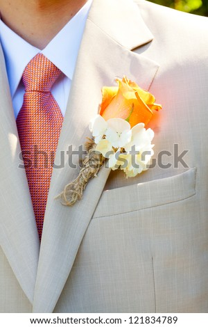 A groom in a light-colored suit is ready for his wedding day in formal attire with a boutineer on his jacket lapel.