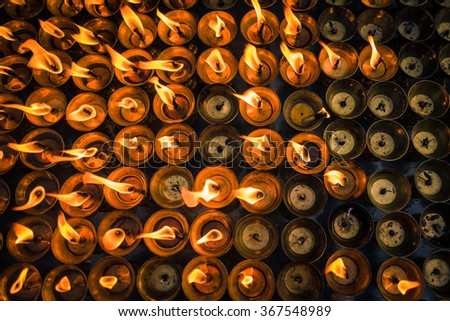 A ground of burning candles lighting up at buddhist temple in Kathmandu,Nepal. Lighting up candles for praying and faith purpose #367548989