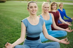 a group of adult women attending yoga outside in the park