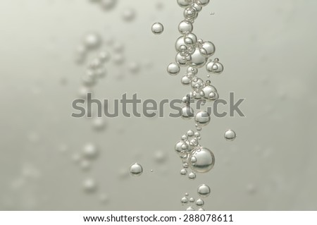 A group of air bubbles rising in a glass of wine