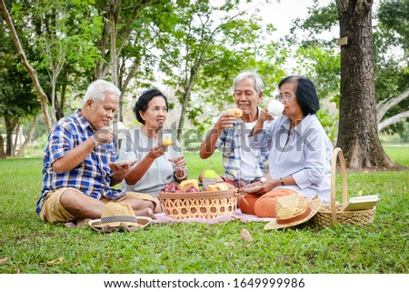 A group of Asian elders are sitting, relaxing and preparing snacks to eat in the shady garden. Watch them happy. Concepts of the elderly community. Picnic at the park