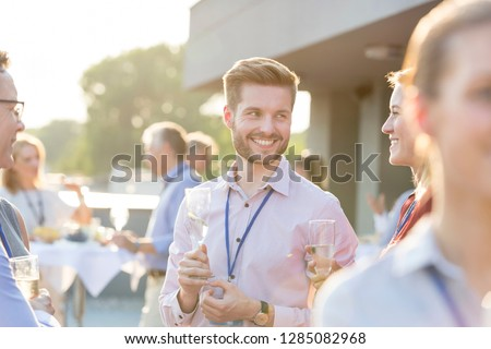 A group of attractive business colleagues enjoying a glass of champagne outside on a roof terrace in a restaurant or a bar. This could be a party, a convention, conference or a wedding event. #1285082968