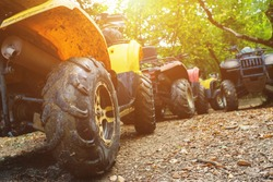 A group of ATVs in a forest covered in mud. Wheels and elements of all-terrain vehicles in mud and clay. Active leisure, sports and tourism