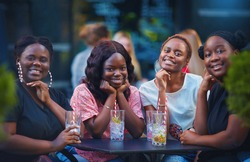 a group of beautiful happy african american women, girls chilling out at summer outdoor cafe, drinking cocktails and having fun