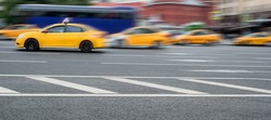 A group of blurred yellow taxicabs in motion in a street of a large city. The concept of urban traffic, comfortable transport, modern city, transportation. Copy space