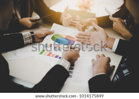 A group of business men and women are meeting together to see graphs about business marketing sales target. teamwork business meeting concept