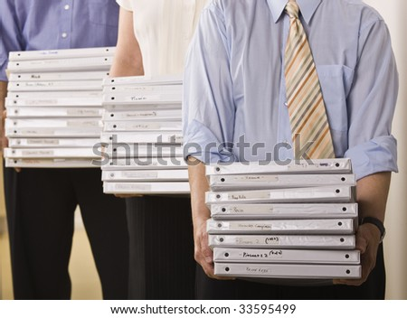 A group of business people are holding binders in an office.  Horizontally framed shot.