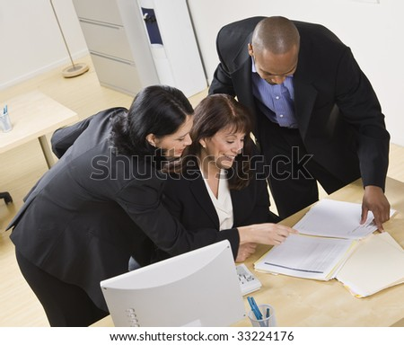 A group of business people are working together in an office. They are looking at paperwork.  Horizontally framed shot.