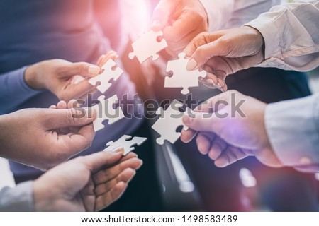 A group of business people assembling jigsaw puzzle. The concept of cooperation, teamwork, help and support in business.