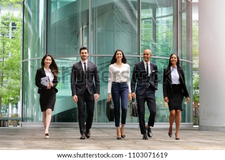 A group of business people of different ethnicities dressed in suits and ties walks proudly after leaving the offices. Concept of: team, success, connection and internationality. #1103071619