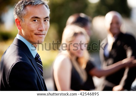 A group of business people outside - sharp focus on Asian man in foreground