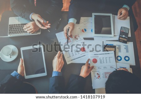 A group of business people talking about the business reports of the project planning board in the meeting room and summarizing the total of privatization of real estate in the project