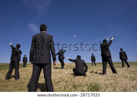 a group of businessman at the field searching for something